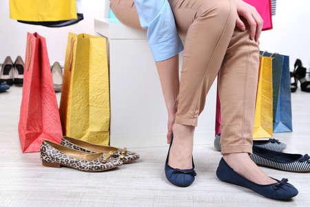 tienda de zapatos: Mujer joven tratando de zapatos en la tienda