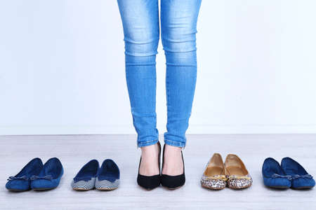 Girl chooses shoes in room on grey  photo
