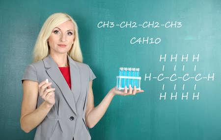 Chemistry teacher explaining formula written on blackboard to her pupils photo