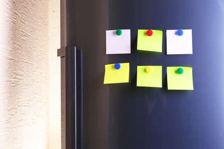 Empty paper sheets and colorful magnets on fridge door photo