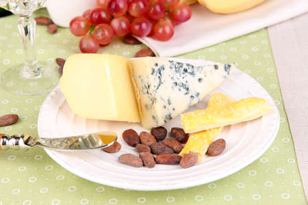 Assorted cheese plate, cocoa beans and grape on pink close-up photo