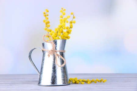 Twigs of mimosa flowers in vase on wooden table photo