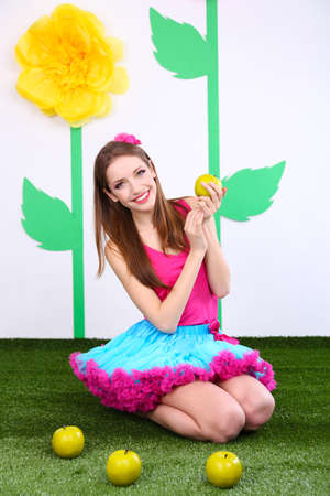 Beautiful young woman in petty skirt with apples  photo