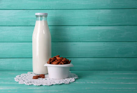 Almond milk in bottle with almonds in bowl, on color wooden background Stock Photo