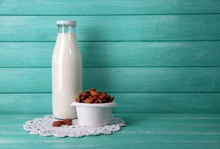 leche: La leche de almendras en botella con las almendras en un tazón, sobre el color de fondo de madera Foto de archivo