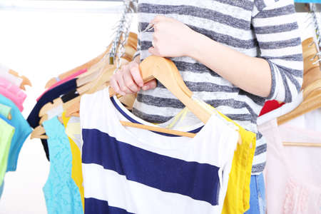 clothes rack: Young woman choose clothes near rack with hangers Stock Photo