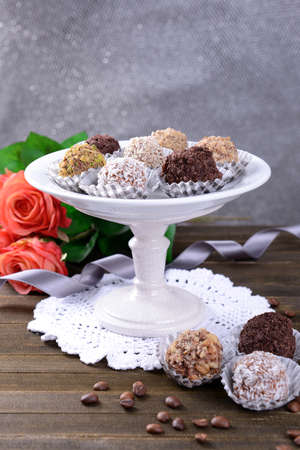 Set of chocolate candies on table on grey background photo