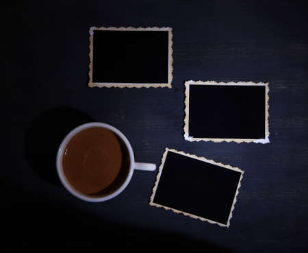 Coffee cup and old blank photos, on wooden background photo