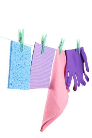 Kitchen sponges and rubber gloves hanging on rope isolated on white photo