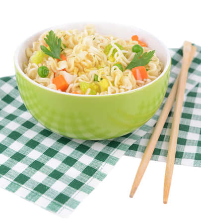 Tasty instant noodles with vegetables in bowl on table close-up photo