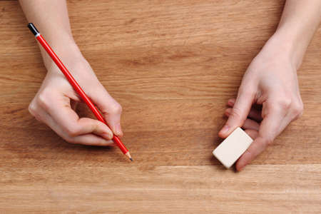 Human hands with pencil and erase rubber on wooden table background photo