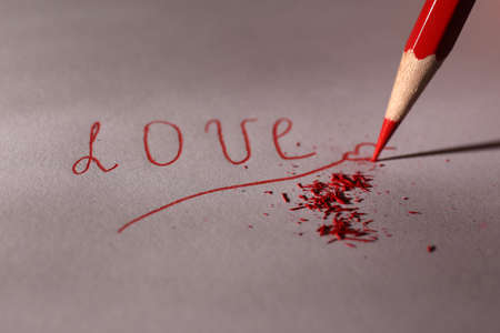 Word Love and breaking pencil on paper, close up photo