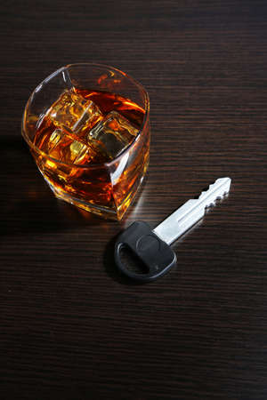 Composition with car key and glass of whiskey, on wooden background photo