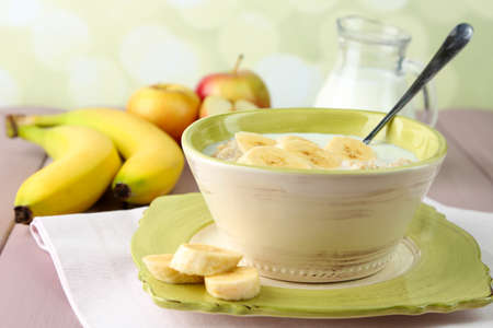 Tasty oatmeal with bananas and milk on table on bright background photo