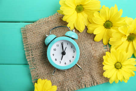 morning blue hour: Alarm clock and beautiful flowers on blue wooden background Stock Photo