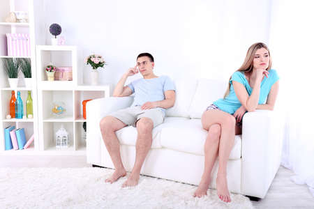 Young man and woman  conflict sitting on sofa argue unhappy, on home interior  photo