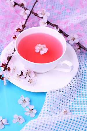 Fragrant tea with flowering branches on wooden table close-up photo