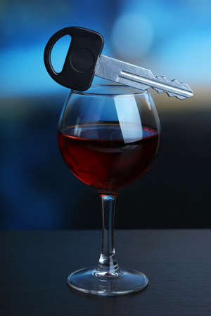 Composition with car key and glass of red wine, on wooden table, on bright background photo