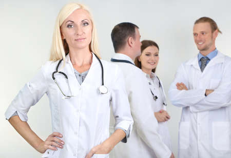 Doctor standing in front of coworkers on grey background photo