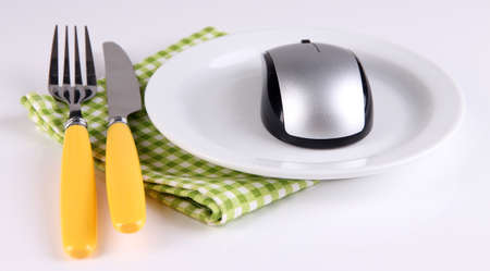 Computer mouse on plate with fork and knife isolated on white photo