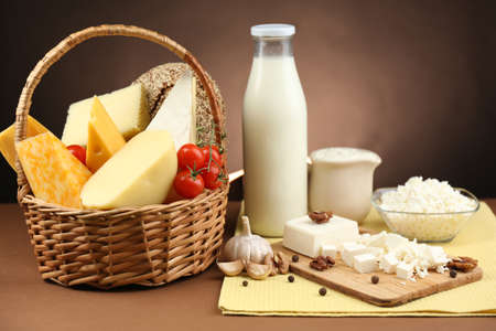 chees: Basket with tasty dairy products on wooden table, on dark brown background