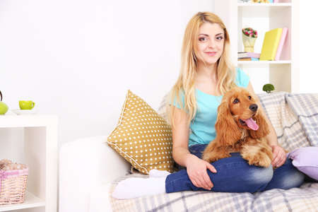 Beautiful young woman with cocker spaniel on couch in room photo