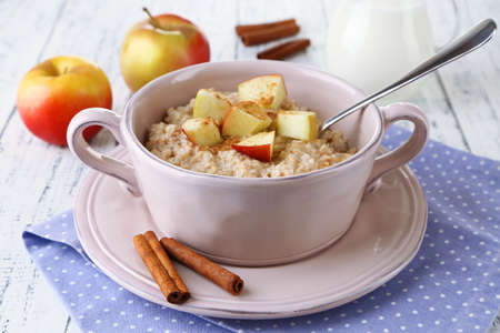 Tasty oatmeal with apples and cinnamon on wooden table photo