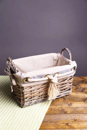 dishcloth: Empty wicker basket on wooden table, on dark background