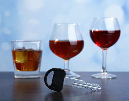 Composition with car key and glasses of drinks, on wooden table, on bright background photo
