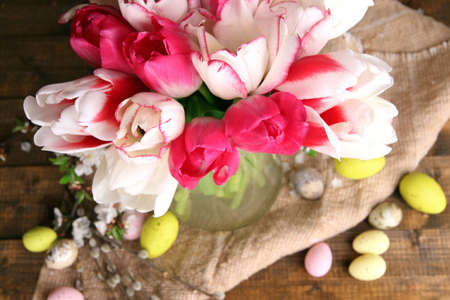 Composition with Easter eggs and beautiful tulips in glass jug on wooden background photo
