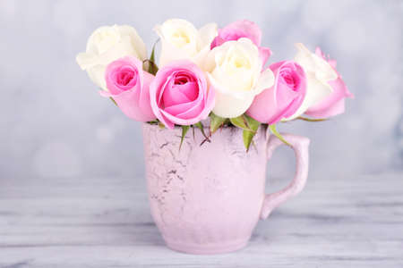 Beautiful roses in cup on light background photo