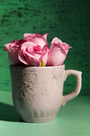 Beautiful roses in cup on green background photo