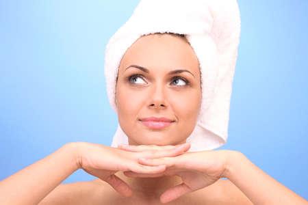Joven y bella mujer después de la ducha con una toalla en la cabeza en azul