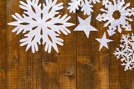 Beautiful paper snowflakes on wooden background photo