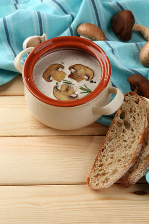 Mushroom soup in pot, on napkin,  on wooden background Stock Photo - 27456081