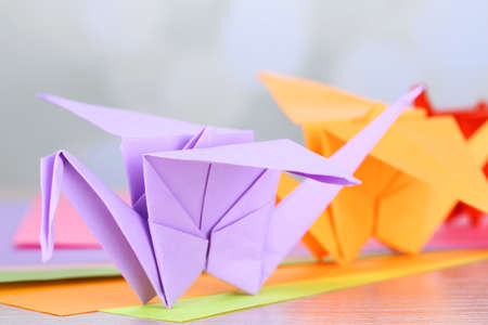 Origami cranes on wooden table, on light background photo