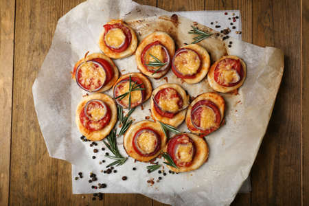 Small pizzas on baking paper close up photo