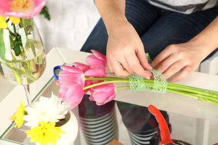 composing: Female hands composing beautiful bouquet, close-up. Florist at work. Conceptual photo