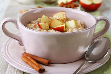 Tasty oatmeal with apples and cinnamon on table close up photo