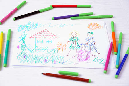Kids drawing of family and colored pencils on wooden\ table