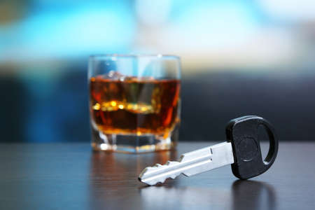 Composition with car key and glass of whiskey, on wooden table, on bright background photo