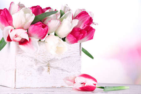 Beautiful tulips  in wooden box, on light background photo