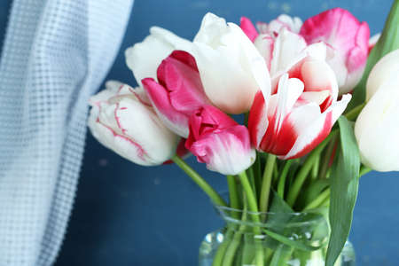 Beautiful tulips in glass jug on color wooden background photo