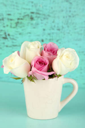 Beautiful roses in cup on blue background photo