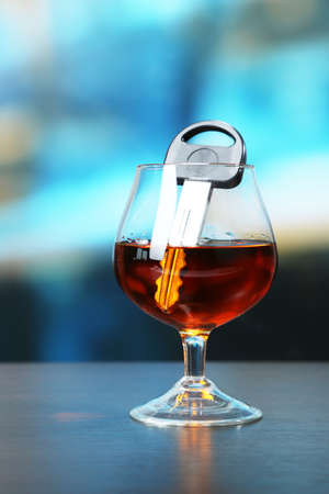 Composition with car key and glass of cognac, on wooden table, on bright background photo