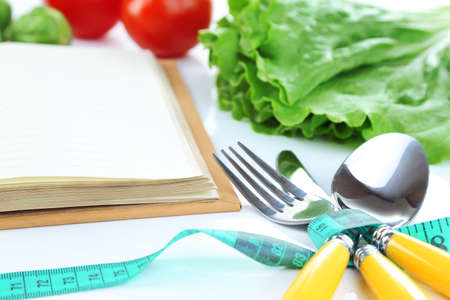 Cutlery tied with measuring tape and book with vegetables close up photo