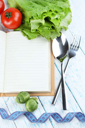 Book with cutlery,measuring tape and vegetables on wooden background photo