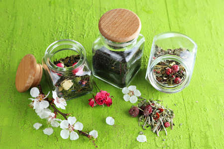 Assortment of herbs and tea in glass jars on wooden background  photo