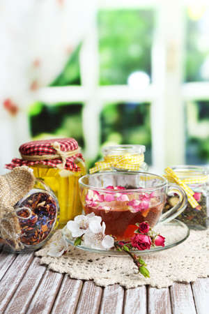 Assortment of herbs,tea and honey in glass jars and cup of hot drink on wooden table, on bright background  photo