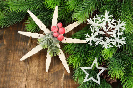 Beautiful snowflakes with fir branch on wooden background photo
